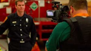 Director and Producer Ted Setla, right, films Schorr in the San Francisco Fire Department headquarters on Sunday.