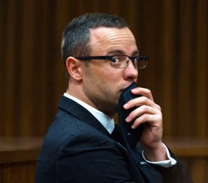 In this photograph taken on Tuesday, May 19, 2014, Oscar Pistorius listens to psychiatric evidence for his defense, during his ongoing murder trial in Pretoria, South Africa. (AP Photo/Daniel Born, Pool, File)