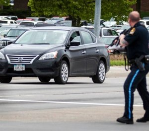 An Omaha police officer points his rifle in the direction of a vehicle headed eastbound on Cuming Street driven by an inmate who escaped from the Pottawattamie County jail in Council Bluffs, Iowa, and carjacked a Nissan Sentra, Monday, May 1, 2017, in Omaha, Neb. (Chris Machian/The World-Herald via AP)
