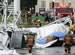 AP Photo/Matt Slocum Firefighters investigate the collapsed canopy.