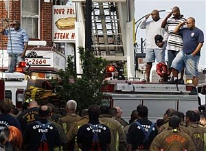 Buffalo firefighters salute as they remove bodies of fellow firefighters. (AP Photo/ David Duprey)