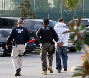 In this March 30, 2012, file photo, Immigration and Customs Enforcement agents take a suspect into custody as part of a nationwide immigration sweep in Chula Vista, Calif. (AP Photo/Gregory Bull, File)