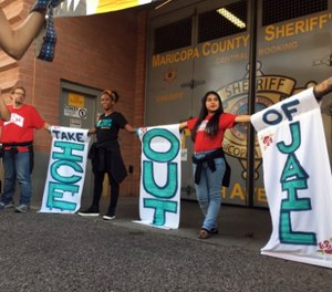 Four activists who chained themselves to each other outside an Ariz. jail entrance were arrested Wednesday. (AP Photo/Astrid Galvan)