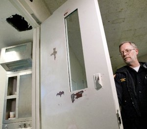 Yakima County Jail spokesman Cpl. Ken Rink shuts the door of the cell number 10 Saturday, Nov. 26, 2005, from which nine inmates escaped Friday night after punching the hole through the ceiling and climbing up onto the facility's roof.