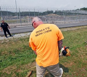 In this Tuesday, July 3, 2012 photo, Lt. Nate Kendrick, left, watches a work crew at the maximum-security Mount Olive Correctional Center in Mount Olive, W.Va. (AP Photo/Steve Helber)
