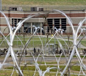 In this Tuesday, July 3, 2012 photo, inmates walk in the yard in front of a cellblock at the maximum-security Mount Olive Correctional Center in Mount Olive, W.Va. (AP Photo/Steve Helber)