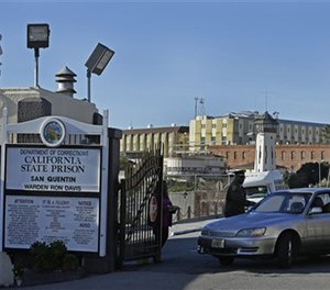 In this Dec. 29, 2015 file photo, a guard checks identification of a person leaving the east gate of San Quentin State Prison. (AP Image)