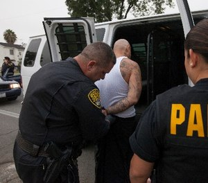 Parole and Special Service Unit agents from the California Department of Corrections and Rehabilitation (CDCR) take a parole violator to jail in Los Angeles Wednesday, July 25, 2012. (AP Photo/Damian Dovarganes)