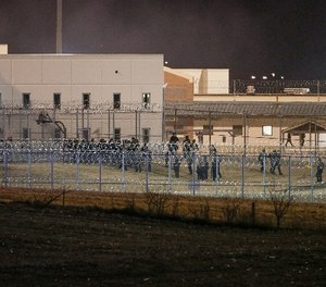 Security forces in riot gear escort prisoners from a courtyard behind razor wire at the Tecumseh State Correctional Institution in Tecumseh, Neb., Thursday, March 2, 2017, where dozens of inmates congregated after refusing to return to their cells. (AP Photo/Nati Harnik)