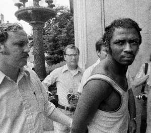 In this Sept. 1, 1973 photo, a federal marshal, left, escorts Herman Bell past members of the media following Bell's capture in New Orleans in connection with the killing of two New York city police officers. (AP Photo)