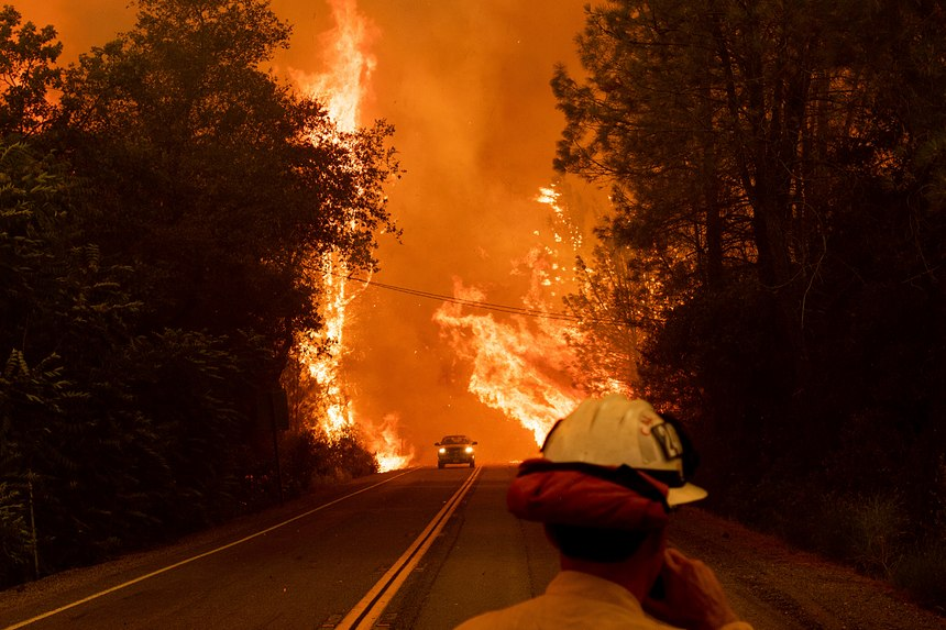 A car passes through flames on Highway 299 as the Carr Fire burns through Shasta, Calif., Thursday, July 26, 2018. Fueled by high temperatures, wind and low humidity, the blaze destroyed multiple homes and at least one historic building. (AP Photo/Noah Berger)