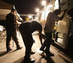 In this file photo, Maricopa County Sheriff's deputies, left, check the shoes of a suspect arrested during a crime suppression sweep in Phoenix. A judge in Arizona on Tuesday, Sept. 18, 2012 ruled that police can immediately start enforcing the most contentious section of the state's immigration law, marking the first time officers can carry out the so-called