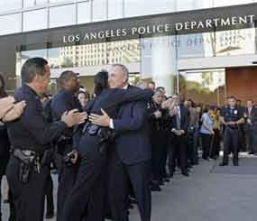 Then-otgoing Los Angeles Police Chief William Bratton and an officer embrace as Bratton exits a ceremony held in his honro at police headquarters in late October 2009. (AP Photo/Reed Saxon)