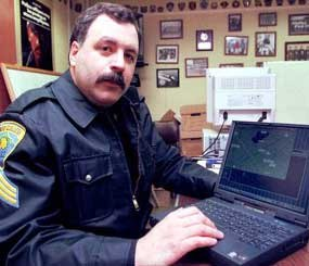A State College (Pa.) Police Officer demonstrates his laptop computer that he uses to assist in fighting crime.