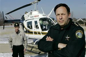 Countryside, Ill., police chief Tim Swanson, right, and pilot Kurt Kaiser stand near an OH-58 helicopter that the city received from the U.S. military as part of a surplus giveaway in Monee, Ill., Friday, Jan. 26, 2007. (AP Photo/Charles Rex Arbogast)