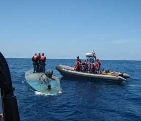 The crew of the U.S. Coast Guard Cutter Jarvis and other U.S. law enforcement agency officials detain a man on a self-propelled semi-submersible vessel during an intercept and seizure in the international waters of the Eastern Pacific off the coast of Guatemala. Guatemalan Defense Ministry spokesman Col. Byron Gutierrez said the semi-sub was detected by Guatemalan personnel operating jointly with the U.S. Drug Enforcement Administration. An undetermined amount of cocaine was seized and the crew of the semi-sub was taken into custody.