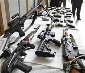 Various guns are displayed at the Chicago FBI offices, Thursday, July 22, 2010. Federal and local authorities say they were seized after 23 people were arrested in and around Chicago by undercover officers. More than 60 guns were seized and the defendants charged with various state and federal weapons and drug violations.