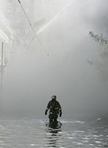 Firefighter walks through floodwater after Katrina