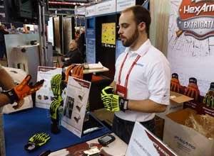 """Photo Rick MarkleyHexArmor's new rescue gloves sell """"like crazy"""" for $35 and $45 at FDIC 2012, according to Patrick Beadling, the company's marketing manager. Marketing Specialist Adam Dietsch (pictured) shows the gloves to a potential customer."""