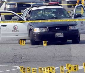 Police tape cordons off the area surrounding an LAPD squad car riddled with bullet holes in the aftermath of an alleged ambush attack by ex-cop Christopher Jordan Dorner. (AP Photo)