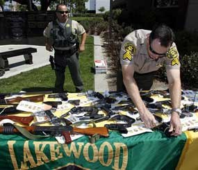 An unidentified Los Angeles County Sheriff's deputy displays weapons confiscated in a gang take down before a news conference Thursday May 21, 2009, in Lakewood, Calif. A Latino street gang waged a racist campaign to eliminate black people from a Southern California city through attempted murders and other crimes, according to federal racketeering indictments. (AP Photo)