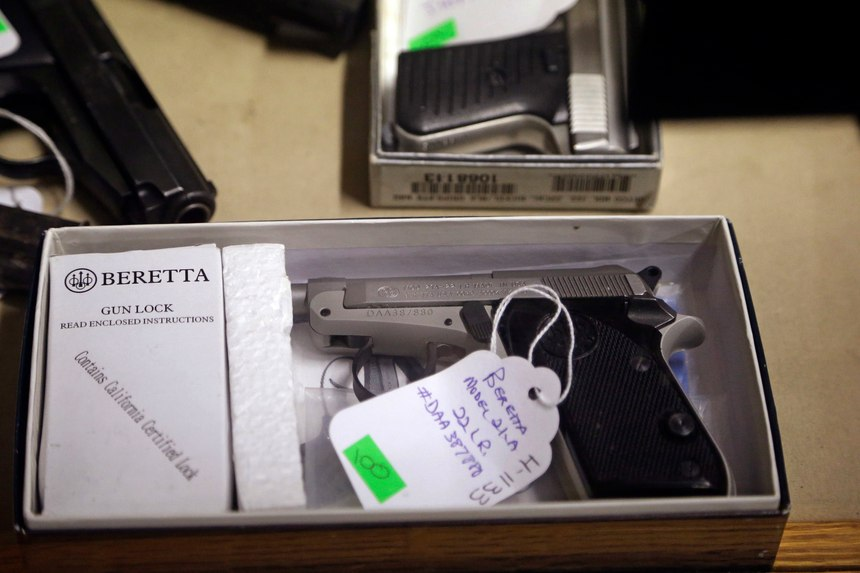 In this Oct. 20, 2017 photo, a Beretta pistol being sold on behalf of the Aberdeen Police Department sits in a gun case before an auction at Johnny's Auction House, where the company handles gun sales for a half dozen police departments and the Lewis County Sheriff's Office, in Rochester, Wash. Law enforcement officials around the U.S. are split over the longtime practice among police departments of selling the guns they confiscate.