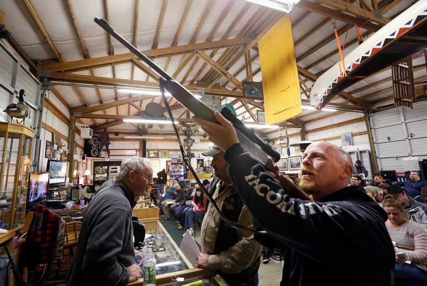 In this Oct. 20, 2017 photo, customer Andy Muscato looks over a rifle before an auction at Johnny's Auction House, where the company handles gun sales for several police departments and the Lewis County Sheriff's Office, in Rochester, Wash. Law enforcement officials around the U.S. are split over the longtime practice among police departments of selling the guns they confiscate. (AP Photo/Elaine Thompson)