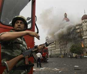 An Indian soldier takes cover as the Taj Mahal hotel burns during gun battle between Indian military and militants inside the hotel in Mumbai, India, Saturday, Nov. 29, 2008. Police said the siege at the Taj Mahal hotel was over after the gun battle, bringing an end to three days of terror in Mumbai in which more than 150 people were killed.