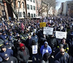 In this March 3, 2011 file photograph, off-duty and retired police officers and firefighters fill a street outside the Statehouse, in Trenton, N.J., during a rally to protest staff cuts and promote public safety. Newark, Trenton, Paterson, Atlantic City and Camden, all densely populated cities with significant crime problems, have made deep cuts in their police departments.