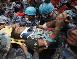 A teen is carried on a stretcher after being rescued by Nepalese policemen and U.S. rescue workers from a building that collapsed during the Nepal 2015 earthquake.