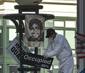 An Oakland public works employee removes signs from a light fixture in Frank Ogawa plaza Monday, Nov. 14, 2011 in downtown Oakland (Calif.). The Occupy encampment was evicted from Frank Ogawa Plaza early this morning. (AP Photo)