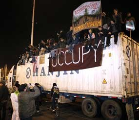 Protestors sit on top of a container truck after blocking the Port of Oakland (Calif.) in mid-December 2011. Occupy protesters shut down the Port of Oakland — the fifth busiest container port in the United States — disrupting the supply chain of countless manufacturers well past the time when the last protester finally went home. (AP Image)