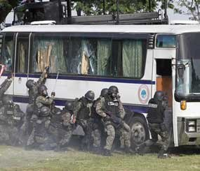 Members of the Philippine National Police Special Action Force demonstrate their skills in bus hostage rescue operation Thursday, Sept. 9, 2010 at the capital command grounds at Camp Bagong Diwa, Taguig city, east of Manila, Philippines. The demonstration was prompted following the botched rescue of tourists who were taken hostage by a dismissed police captain. The incident left eight hostages dead.