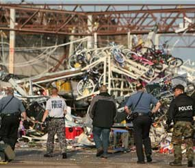 Police officers walk in to the back of a destroyed store in Joplin (Mo.), where scores were killed and hundreds more injured when a tornado cut a destructive path through the town Sunday evening. (AP Photo)