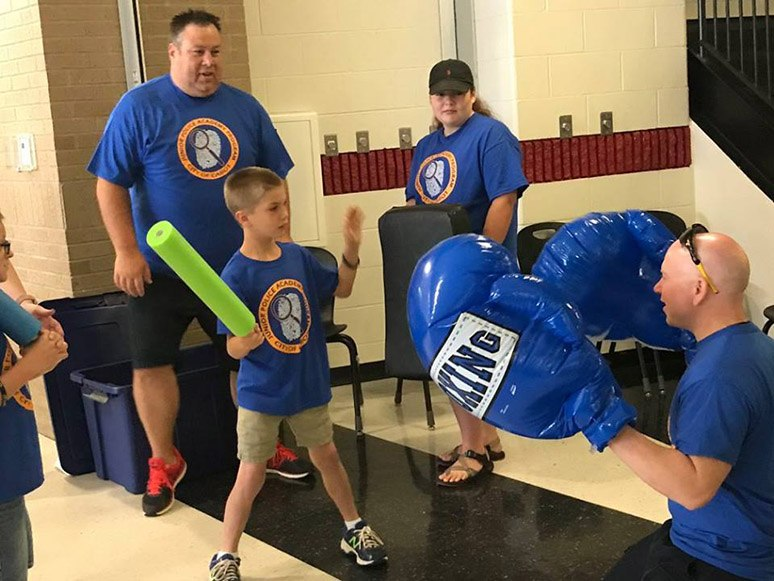Cabot PD staff and volunteers help cadets practice baton skills.