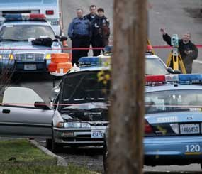 Police work at the scene where a man suspected of gunning down four police officers was shot and killed by a lone Seattle patrol officer who came across the stolen car in a south Seattle neighborhood about 2:45 a.m.