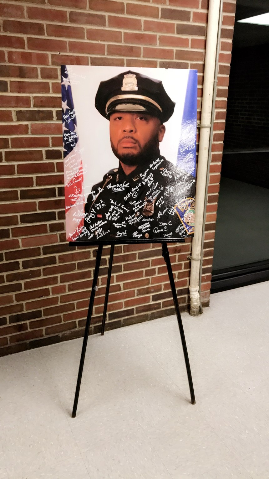 At a memorial ceremony, signatures cover an image of D.J.