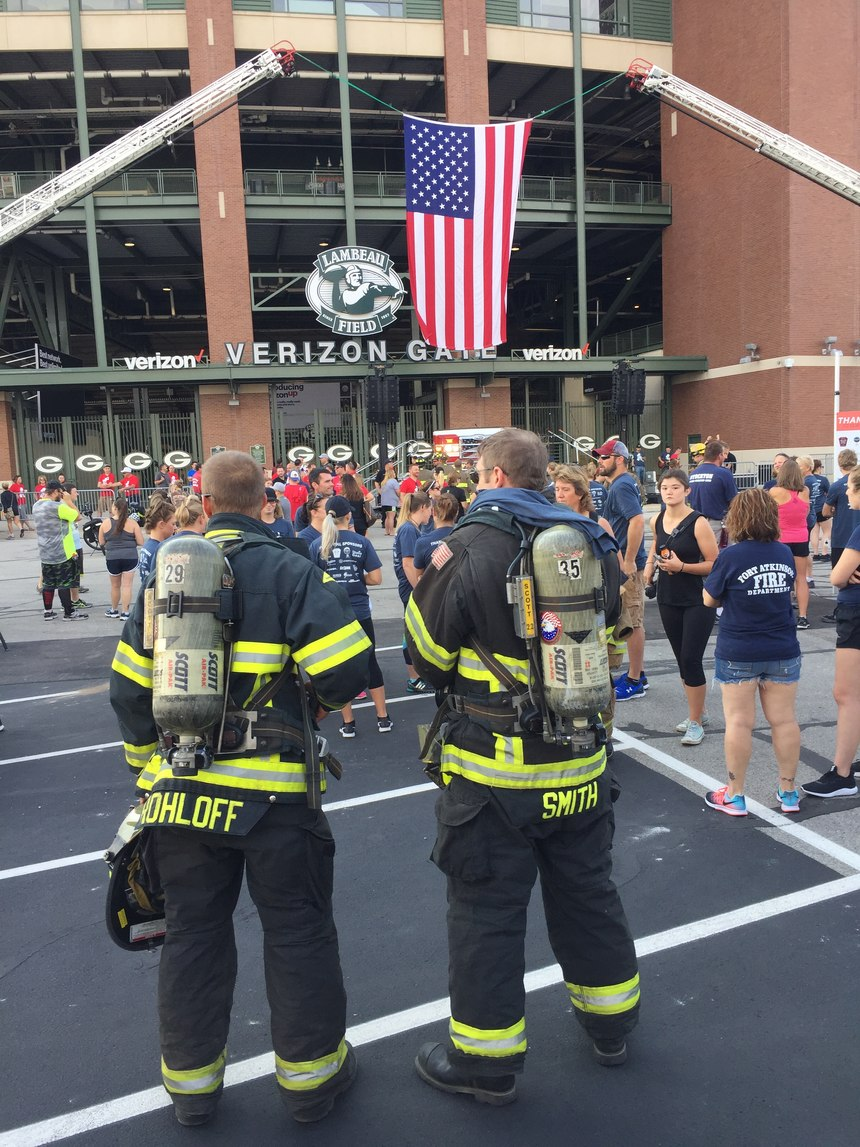 Firefighters and civilians gather outside Lambeau Field before the start of the climb.