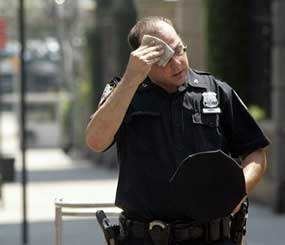A New York City police officer wipes his face next during an August 2006 heat wave in New York. (AP Photo)