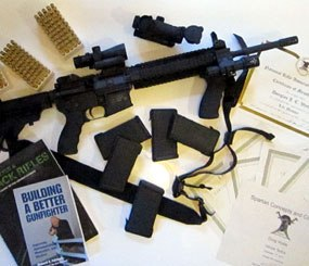 The Wyllie family AR-15, displayed with a variety of my top-choice accessories, including a two of my favorite firearms books, a number of my firearms training certificates, and my NRA Lifetime Membership certificate, carefully removed from its frame.
