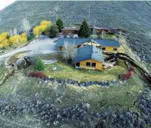This aerial image provided by Tributary Environmental shows a home damaged by a landslide Friday, April 18,in Jackson, Wyo. A slow-moving landslide in Jackson sped up significantly Friday, splitting this house in two, causing a huge uplift in a road and a Walgreens parking lot, and threatening to destroy several other unoccupied homes and businesses. (AP Photo/Tributary Environmental)