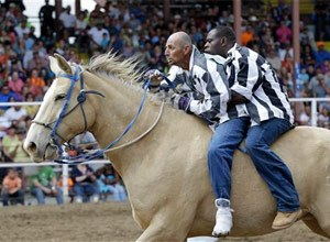 Inmates ride a horse in the Buddy Pick-Up event at the Angola Prison Rodeo in Angola, La., Saturday, April 26, 2014. (AP Photo/Gerald Herbert)