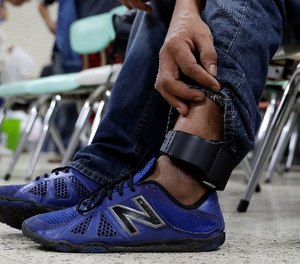 In this Sunday, Nov. 13, 2016, photo, Luis Carlos, a construction worker from Honduras who is headed to Miami with his son, wears an ankle monitor as he sits at the Sacred Heart Community Center in the Rio Grande Valley border city of McAllen, Texas after he was released after processing by U.S. Customs and Border Patrol.