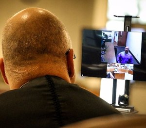 Kern County Superior Court Judge David Wolf speaks with an inmate at Pelican Bay State Prison, 600 miles away via an Oct. 16 video arraignment at Delano Prison Court (illustration).