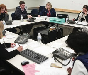 People answer phones at the call center for Hepatitis A questions at the Utah County Health Department.