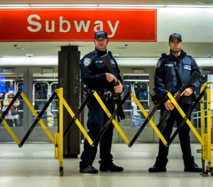 Police stand guard inside the Port Authority Bus Terminal following an explosion near Times Square on Monday, Dec. 11, 2017, in New York. (AP Photo/Andres Kudacki)