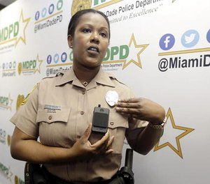 Miami-Dade Police Department PIO Marjorie Eloi shows how to turn on and off a body camera, which 1,000 officers will begin using over the next few months, during a news conference, Thursday, April 28, 2016.