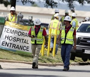 Construction workers leave a temporary entrance to Coryell Memorial Healthcare System hospital where an explosion in a building under construction injured several people, and knocked power out for a large portion of the city. (Photo/AP)