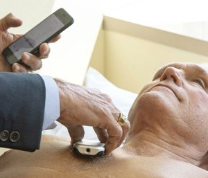 James Thomas, a cardiologist at Northwestern Hospital in Chicago examines Dennis Calling, a retired Chicago inspector, using Eko Duo, a new device for cardiovascular screening.