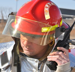Mike Fortmann of the 128th Air Refueling Wing Fire Department, Milwaukee, communicates with headquarters via a handheld radio during a training exercise.